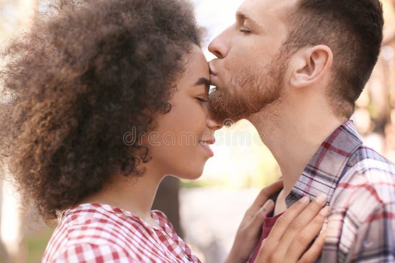 Hombre joven que besa a su novia afroamericana hermosa al aire libre imágenes de archivo libres de regalías