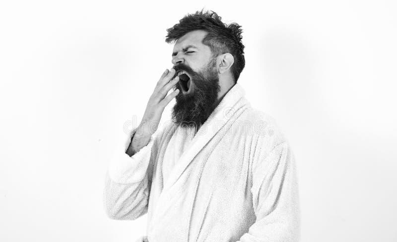 Hombre joven que bosteza con el suyo boca abierta de par en par Inconformista en la albornoz blanca aislada en el fondo blanco Ma imágenes de archivo libres de regalías
