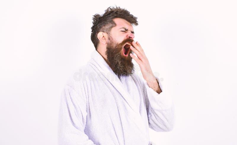 Hombre joven que bosteza con el suyo boca abierta de par en par Inconformista en la albornoz blanca aislada en el fondo blanco Ma foto de archivo libre de regalías