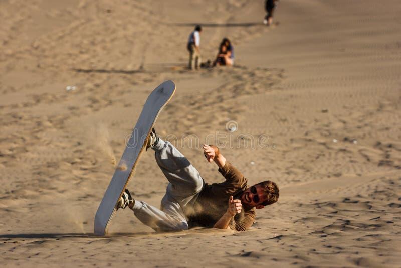 Hombre joven que cae mientras que sandboarding en la puesta del sol, Huacachina, AIC, imágenes de archivo libres de regalías