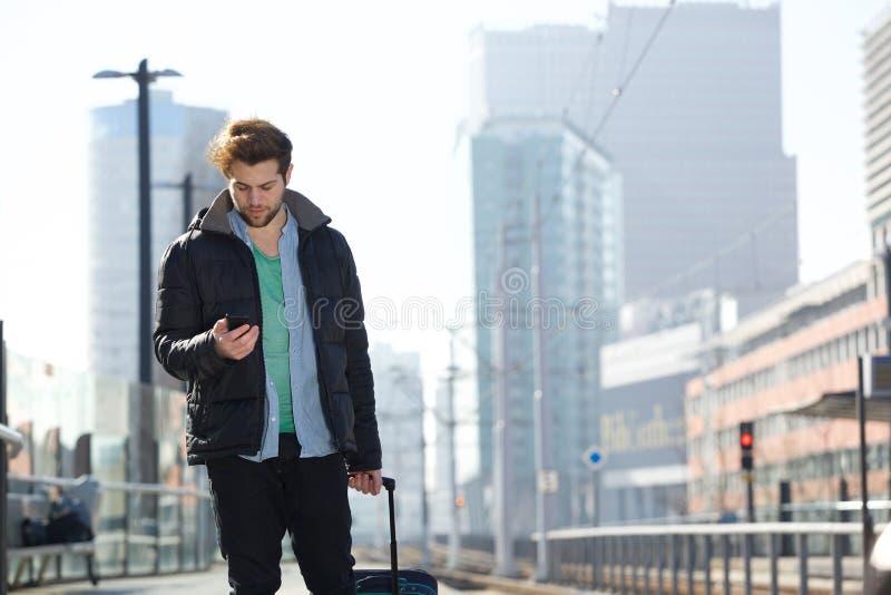 Hombre joven que camina con el bolso y el teléfono móvil en la ciudad fotos de archivo libres de regalías