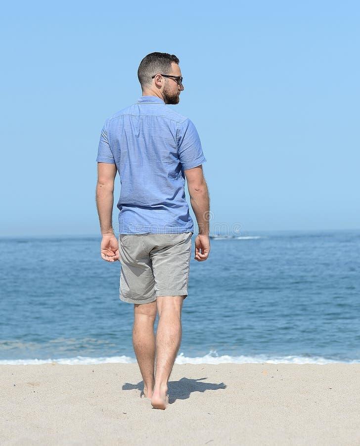 Hombre joven que camina en la playa arenosa imagen de archivo libre de regalías