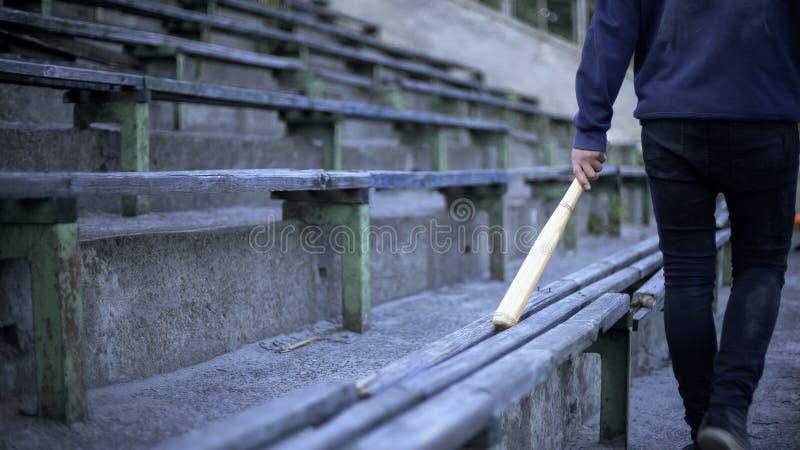 Hombre joven que camina en tribuna del estadio con el bate de béisbol, cuadrilla de juventud, vandalismo imágenes de archivo libres de regalías