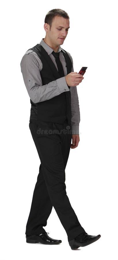 Hombre joven que camina mientras que comprueba su móvil foto de archivo