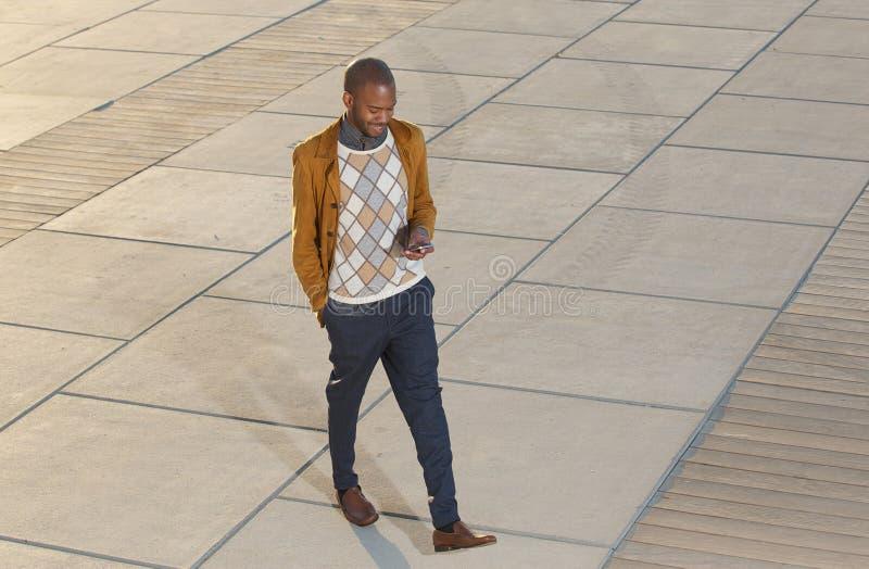 Hombre joven que camina y que envía el mensaje en el teléfono móvil imagen de archivo libre de regalías