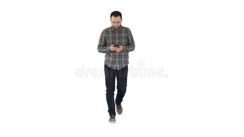 Hombre joven que camina y que usa un teléfono, mensajería en el fondo blanco imágenes de archivo libres de regalías