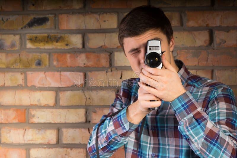 Hombre joven que captura algo usando cámara imagen de archivo