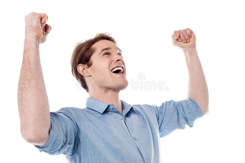 Hombre joven que celebra éxito con los brazos para arriba imagenes de archivo