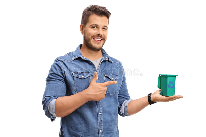 Hombre joven que celebra una pequeños papelera de reciclaje y señalar fotografía de archivo libre de regalías