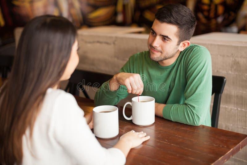 Hombre joven que come café con su fecha fotografía de archivo