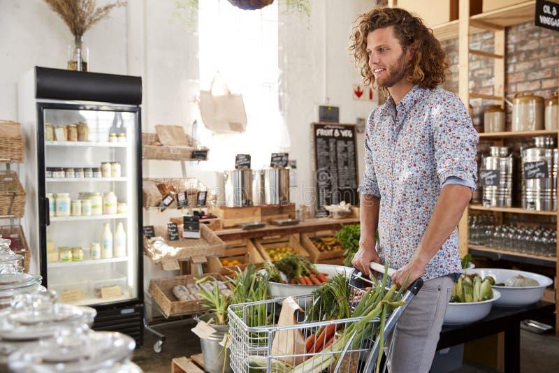 Hombre joven que compra fruta y verdura fresca en colmado libre plástico sostenible fotografía de archivo