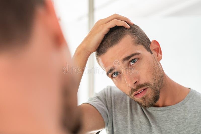 Hombre joven que comprueba el pelo en espejo fotos de archivo libres de regalías