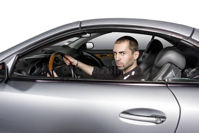 Hombre joven que conduce su nuevo coche foto de archivo