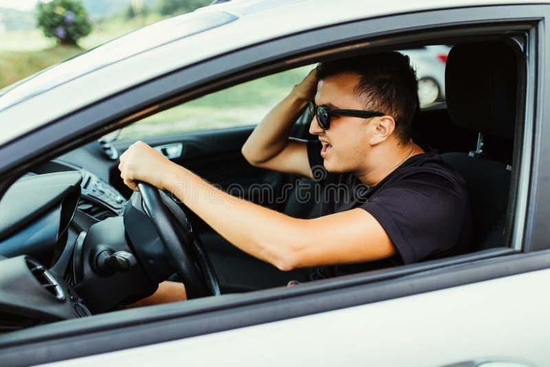 Hombre joven que conduce un coche chocado alrededor para tener accidente de tráfico, opinión de la ventana fotografía de archivo libre de regalías