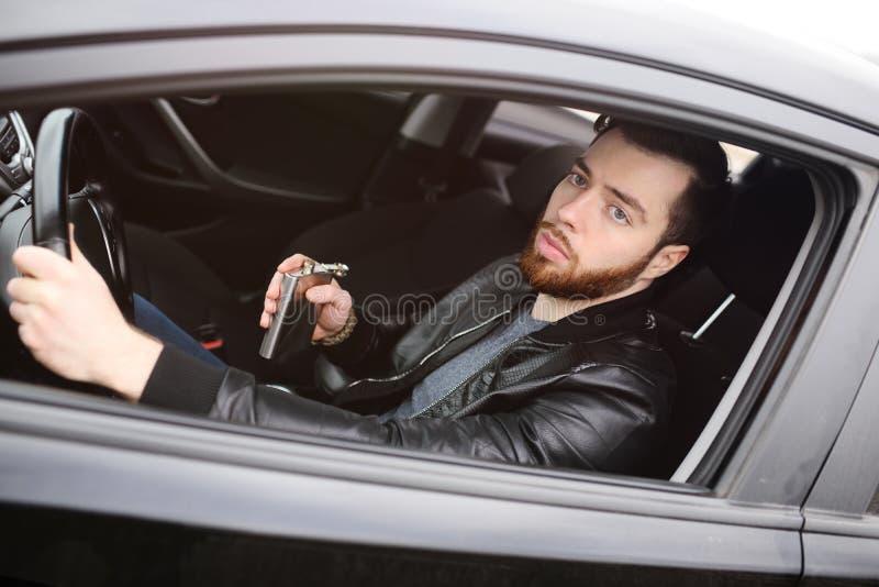 Hombre joven que conduce un coche con un frasco del hierro imagen de archivo libre de regalías