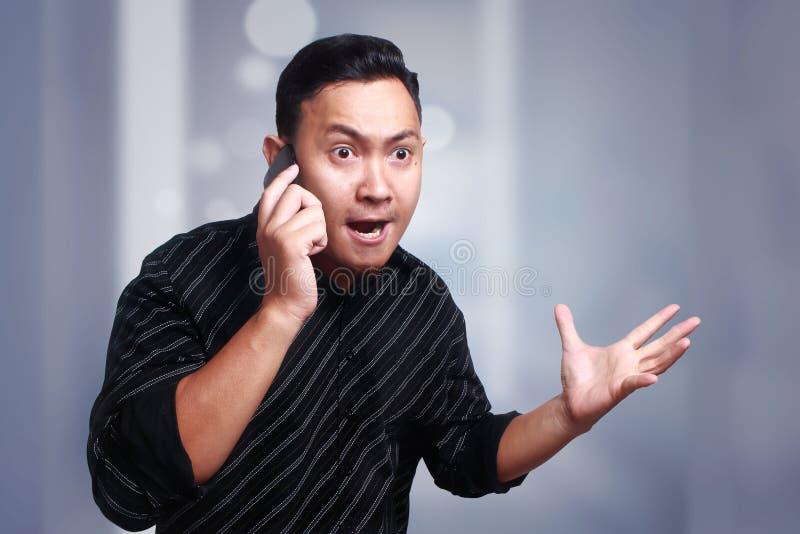 Hombre joven que consigue malas noticias en el teléfono, chocado y enojado fotos de archivo