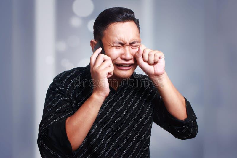 Hombre joven que consigue malas noticias en el teléfono, chocado y el griterío imagenes de archivo