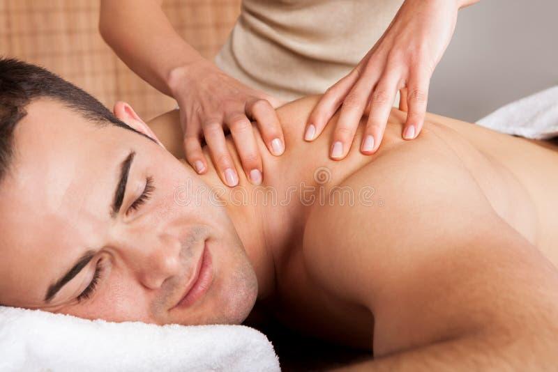 Hombre joven que consigue masaje del hombro fotografía de archivo