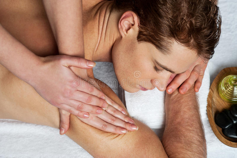 Hombre joven que consigue masaje en balneario imagen de archivo