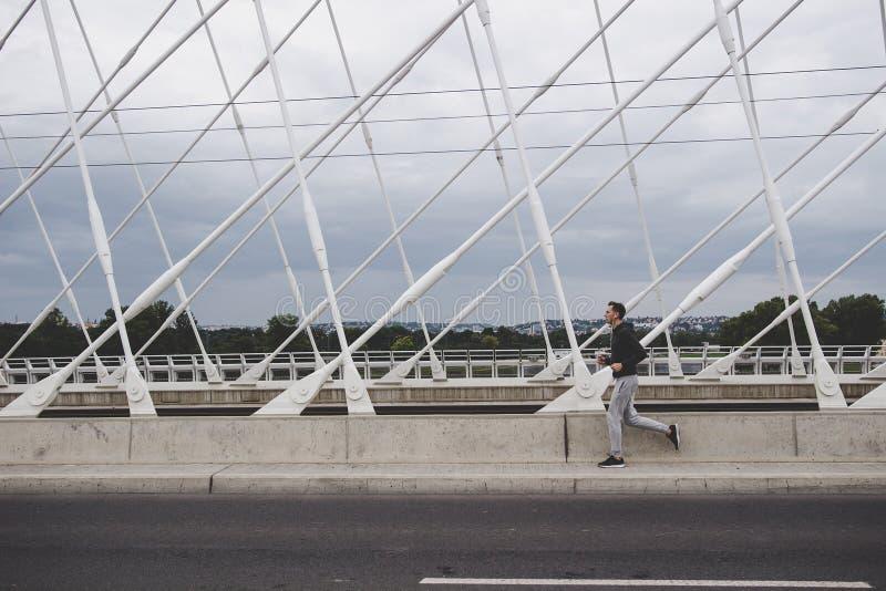 Hombre joven que corre en el puente moderno en la ciudad, música que escucha en smartphone foto de archivo