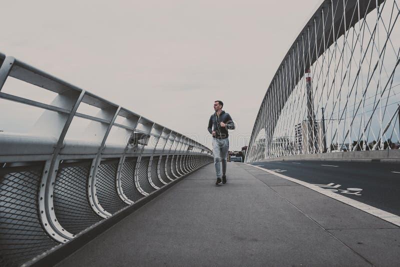 Hombre joven que corre en el puente moderno en la ciudad, música que escucha en smartphone fotos de archivo libres de regalías
