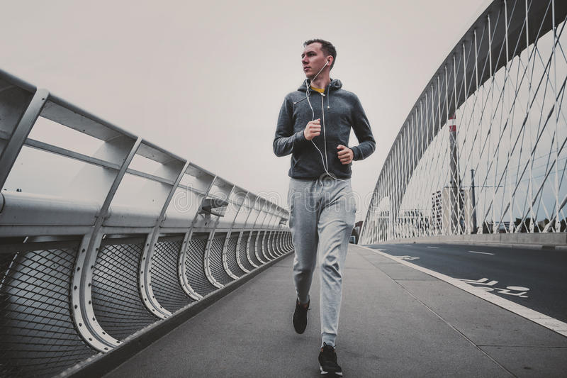 Hombre joven que corre en el puente moderno en la ciudad, música que escucha en smartphone fotos de archivo