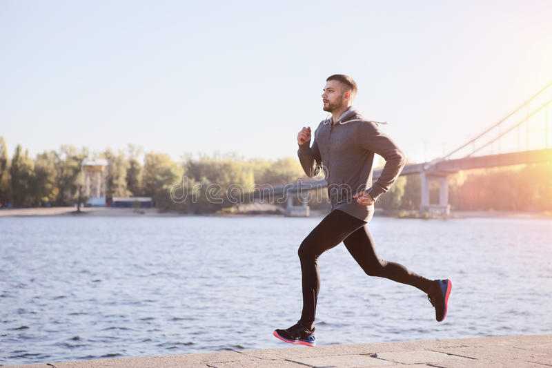 Hombre joven que corre a lo largo del terraplén del río imagen de archivo libre de regalías