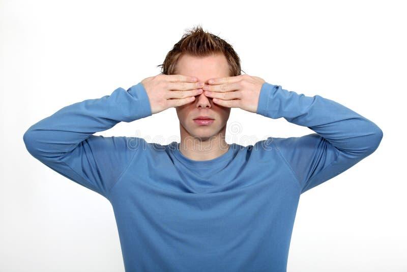 Hombre joven que cubre sus ojos foto de archivo libre de regalías