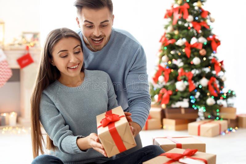 Hombre joven que da el regalo de la Navidad a su novia imagenes de archivo