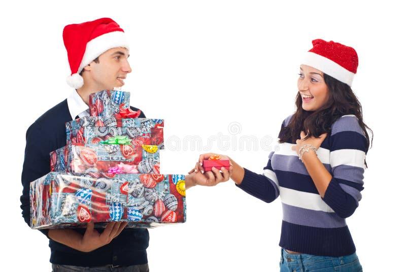 Hombre joven que da el regalo de la Navidad a una mujer imagen de archivo