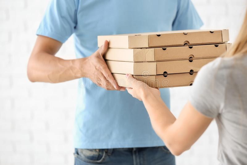 Hombre joven que da las cajas de la pizza a la mujer en el fondo blanco Servicio de entrega de la comida fotos de archivo