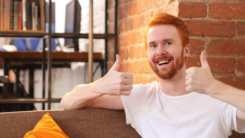 Hombre joven que da los pulgares para arriba mientras que sonríe en el trabajo, oficina imagenes de archivo