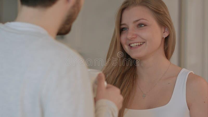 Hombre joven que da un beso de la buena mañana a su esposa en la cocina fotografía de archivo