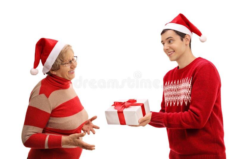 Hombre joven que da un regalo de Navidad a la señora mayor imágenes de archivo libres de regalías