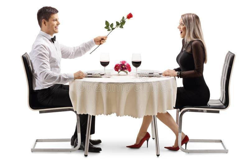 Hombre joven que da una rosa roja a una mujer joven en una tabla del restaurante fotos de archivo