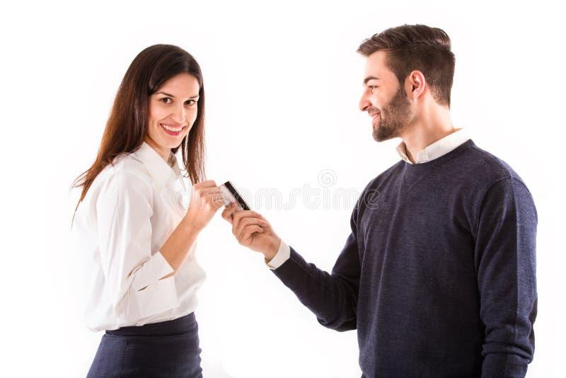 Hombre joven que da una tarjeta de crédito a la mujer joven imágenes de archivo libres de regalías