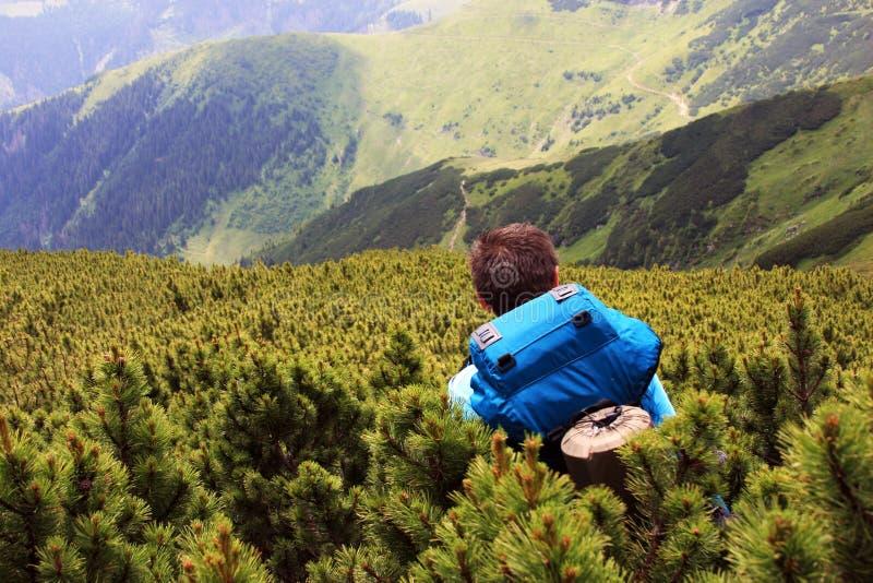 Hombre joven que desciende de la montaña imagenes de archivo