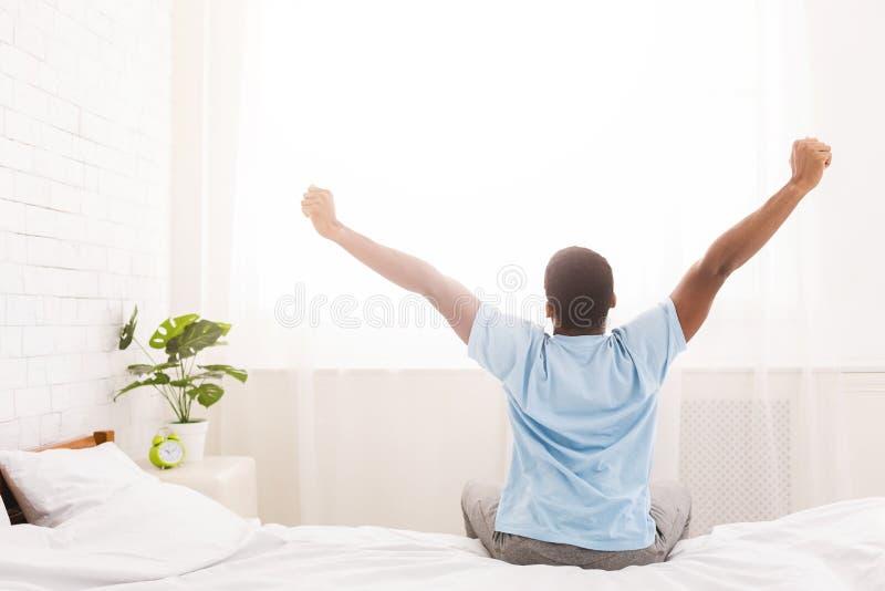 Hombre joven que despierta en cama y que estira sus brazos fotos de archivo