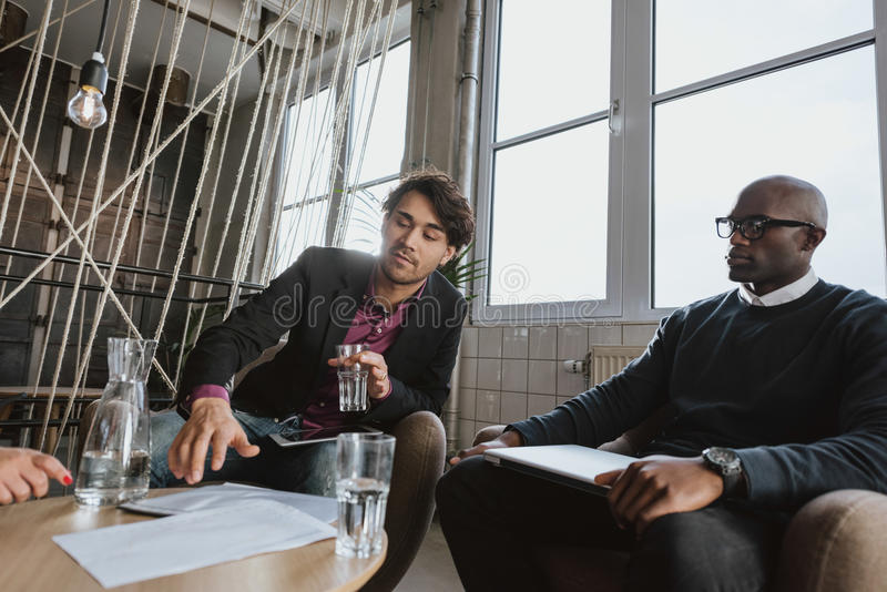 Hombre joven que discute estrategia empresarial con los colegas fotos de archivo libres de regalías