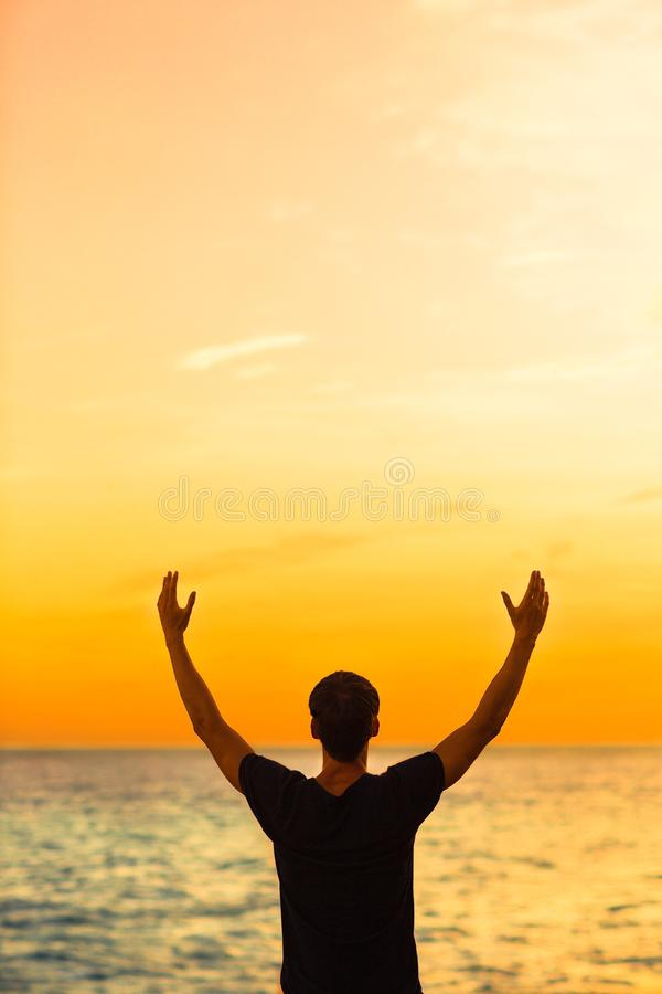 Hombre joven que disfruta de la puesta del sol con sus brazos en el aire Feliz y libre fotografía de archivo