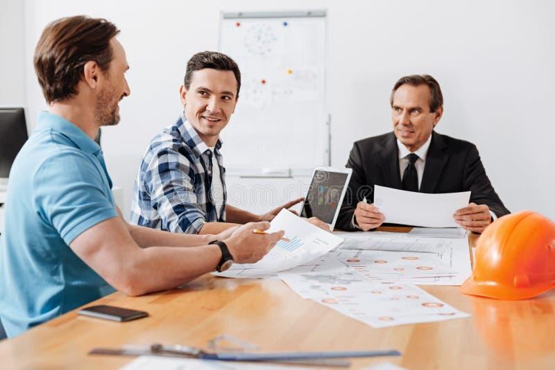 Hombre joven que divulga a su jefe durante la reunión imagenes de archivo