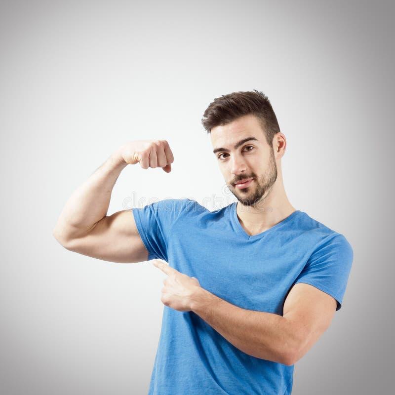 Hombre joven que dobla el retrato del músculo del brazo del bíceps imagen de archivo libre de regalías
