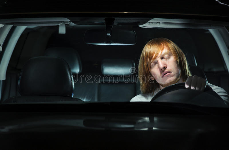 Hombre joven que dormita apagado mientras que conduce en la noche imágenes de archivo libres de regalías