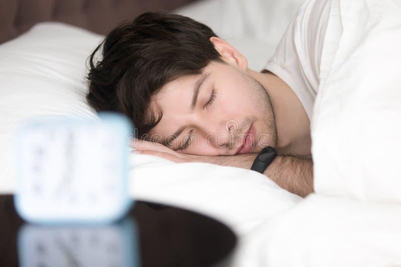 Hombre joven que duerme al lado del despertador que lleva pulsera elegante fotos de archivo libres de regalías