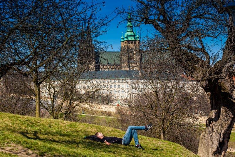 Hombre joven que duerme debajo de los árboles del parque de Petrin con la catedral de Praga en fondo fotografía de archivo