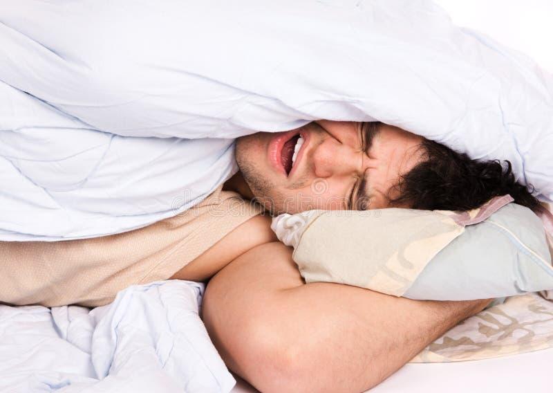 Hombre joven que duerme en cama fotos de archivo