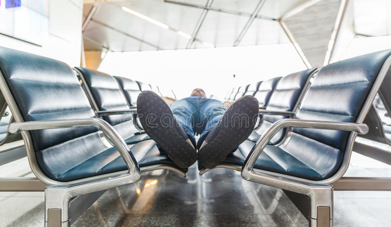 Hombre joven que duerme en el aeropuerto imagen de archivo
