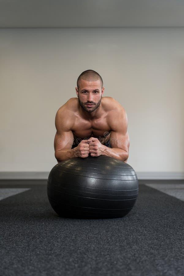 Hombre joven que ejercita con ejercicio del ABS de la bola de la aptitud fotografía de archivo