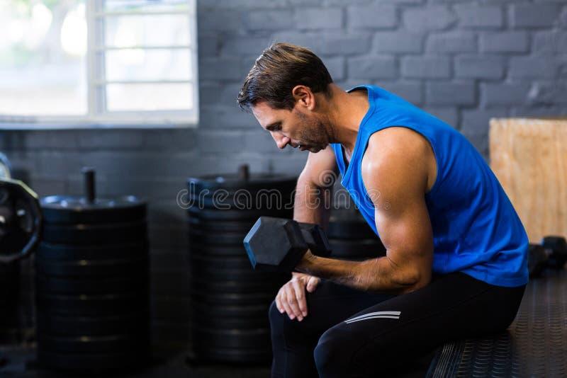 Hombre joven que ejercita con pesa de gimnasia imágenes de archivo libres de regalías