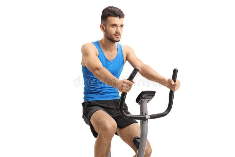 Hombre joven que ejercita en una bici inmóvil fotos de archivo